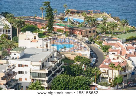 LOS GIGANTES, SPAIN - OCTOBER 07: Tropical morning sun is illuminating the ocean coast, building and vacationers people at area of Avenue Jose Gonzalez Forte on October 07, 2014 in Los Gigantes, Tenerife, Canary Islands, Spain.