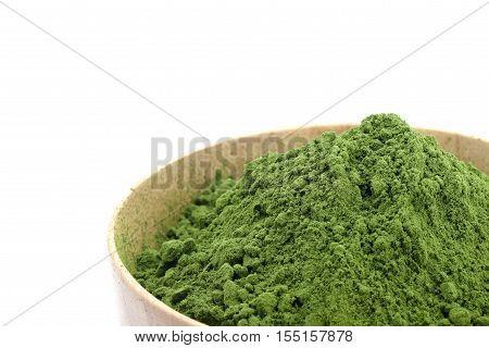 Green tea powder in woodbowl on white background.