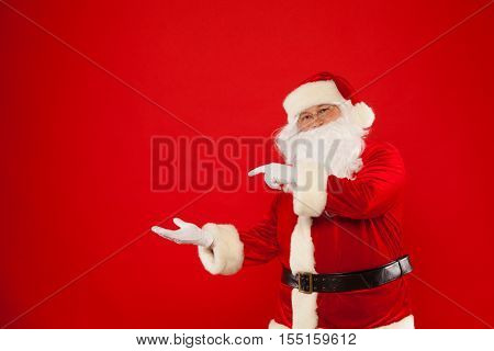 Santa Claus pointing in blank a place, red background. Merry Christmas
