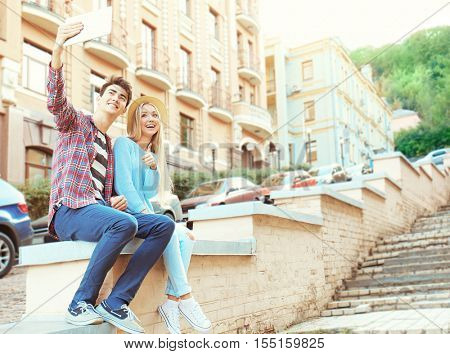 Smiling couple taking selfie with tablet on the street