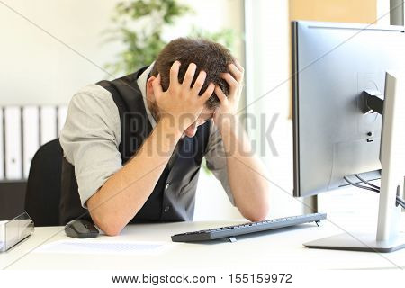 Depressed businessman after bankruptcy lamenting with hands on the head in a desktop in the office