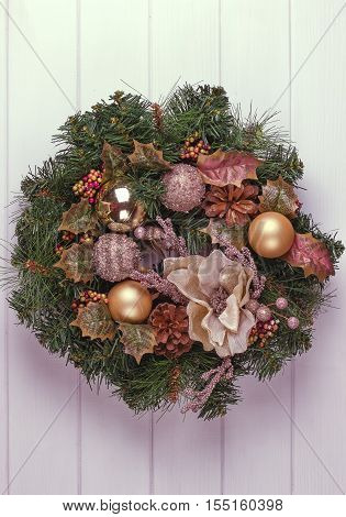 Christmas wreath on a rustic wooden white front door.