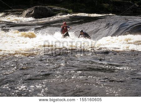 KOLA PENINSULA RUSSIA - 17 AUGUST 2008: Men on an inflatable catamaran overcome the threshold of the turbulent river. Catamaran is not visible.