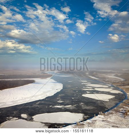 Aerial view of the great river with floating ice floes during the spring day. Drifting of ice.Driving of ice. Ice floe.