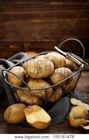 fresh raw potato in basket on wooden background