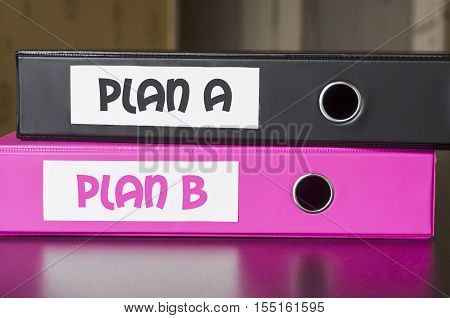 Bright office folders over dark background and plan a and plan b text concept