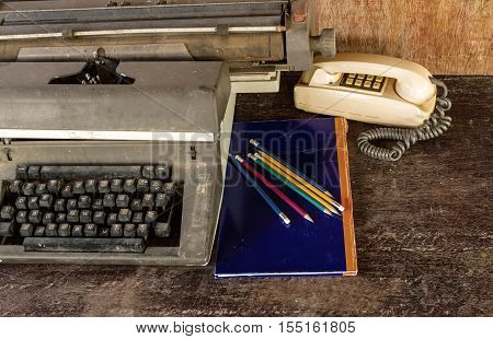 Vintage typewriter blue book pencil and old telephone on old wooden touch-up in still life concept
