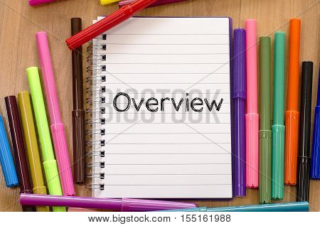 Human hand writing overview on notepad .