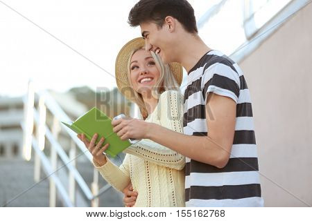 Young couple looking at travel guide outdoors