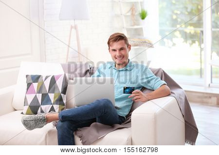 Young happy man with laptop and credit card making online shopping
