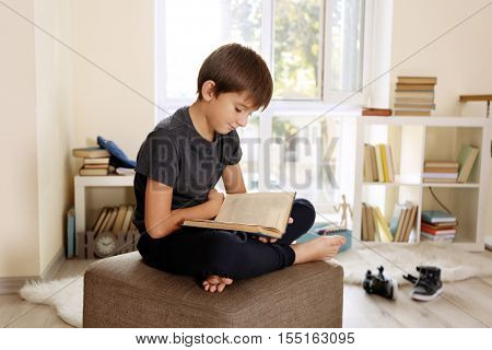Cute schoolboy reading interesting book on pouf in room