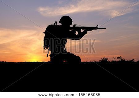Silhouettes of soldier on sunset background. Military service concept.