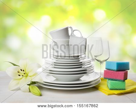 Clean tableware dishwashing sponges and lily flower over abstract background