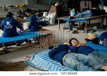 Bangkok, Thailand - November 10, 2008 :  On a building site in Bangkok during lunch time, workers have a break, some have a short nap. Most workers come from the north east of Thailand, Cambodia and Myanmar.