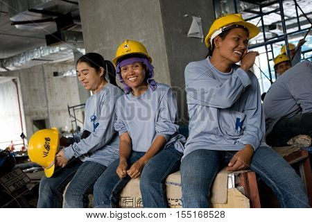 Bangkok, Thailand - November 10, 2008 :  On a building site in Bangkok during lunch time, workers have a break. Most workers come from the north east of Thailand, Cambodia and Myanmar.