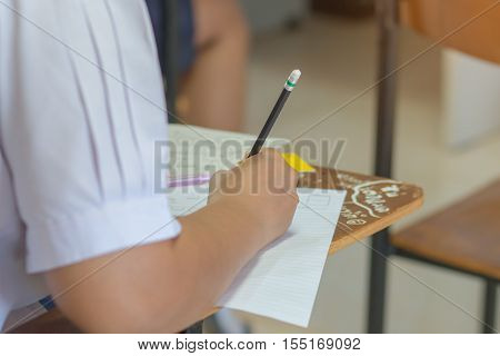 Asian students reading and writing a test in test paper exercise exam in classroom : education concept