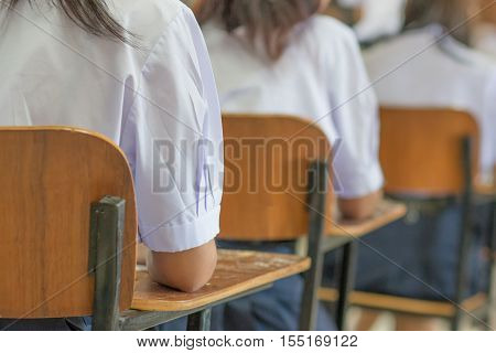 Asian students reading and writing a test in exercise exam in classroom : education concept