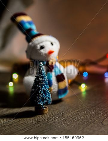 cute Christmas white snowman in a hat and a little Christmas toy tree in the background lights with place for text as substrate