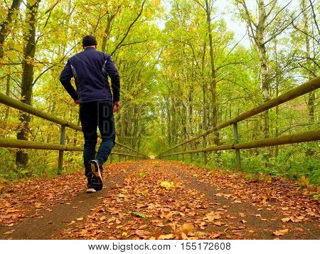 Sportsman In  Black Sortswear Run On Road Covered By Autumn Leaves.