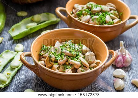 Cooked broad beans with parsley on old wooden table