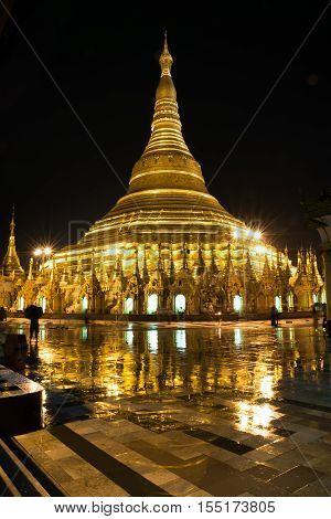Shwedagon pagoda at night with reflection on the floor after the rain, Yangon, Myanmar