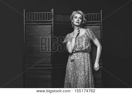 Beautiful blond young woman in dress standing near wooden folding screen. Studio shot on black background. Copy space. Monochrome.