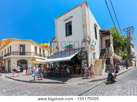 Rethymnon, Island Crete, Greece - July 1 2016: A local citizen on the scooter and tourists are walking on the street and sitting in cafe with Italian food on the street of the old town's part of city Rethymnon