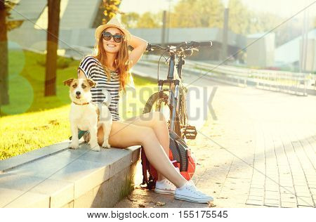 Smiling Hipster Girl with her Dog and Bike in City. Happy Woman Enjoying Summer Lifestyle with Pet in Park. Teenage Female Leisure. Toned and Filtered Photo with Copy Space.
