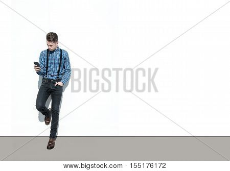 Modern Young Man Standing By White Wall, Using His Phone