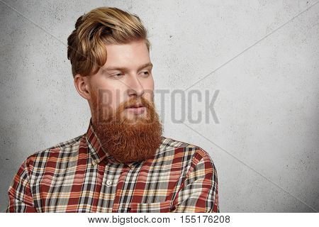 Portrait Of Young Caucasian Brutal Man With Fuzzy Beard Wearing Red Checkered Shirt Looking Away Wit