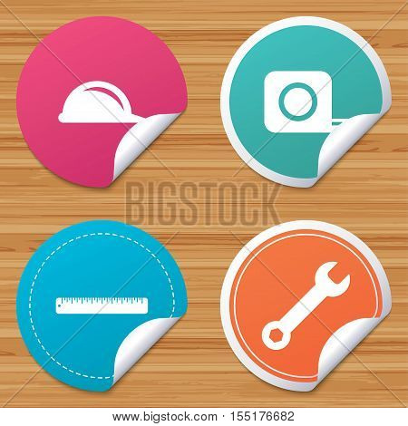Round stickers or website banners. Construction helmet and wrench key tool icons. Ruler and tape measure roulette sign symbols. Circle badges with bended corner. Vector