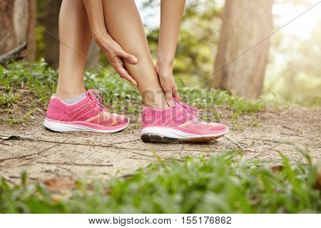 Running Sport Injury. Female Athlete Jogger Wearing Pink Sneakers Touching Her Twisted Or Sprained A