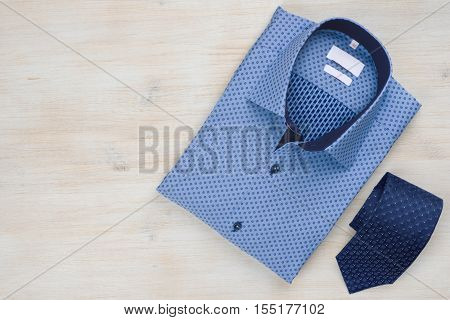 Folded blue man shirt and tie isolated on wooden background