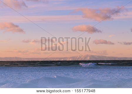 Sunset on Baikal Lake. Ice and water ridges on the lake Baikal. Siberia Russia