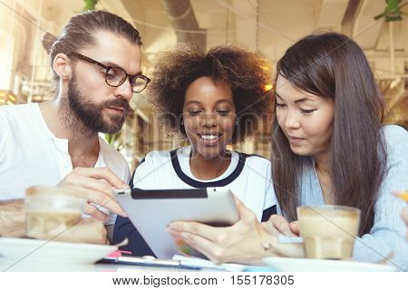 Teamwork and cooperation concept. Three talented young ambitious people brainstorming having discussion on common project using digital tablet at cafeteria. Multiethnic group working on touch pad