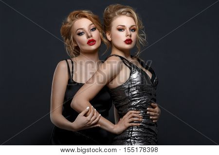 Two beautiful young women in evening mini dresses. Red lips. Over dark background. Copy space.