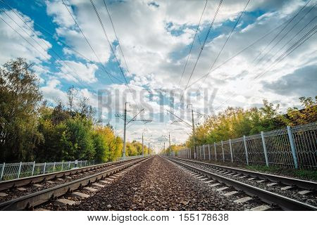 Railway tracks in a rural forest with white clouds. Empty railroad lines going to horizon.