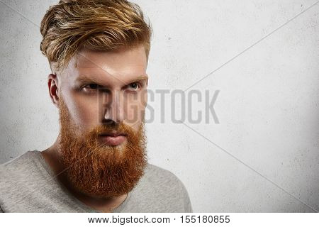 Headshot Of Fashionable Young Hipster Man With Thick Beard And Stylish Haircut Looking Into Distance
