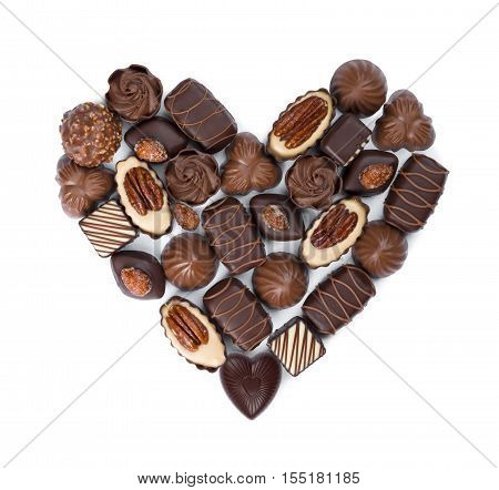 Heart shape made from various chocolate bonbons isolated on white