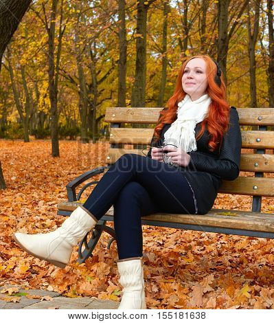 girl in autumn season listen music on audio player with headphones, sit on bench in city park, yellow trees and fallen leaves