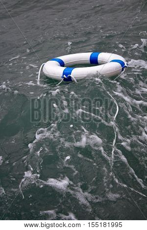 Lifebuoy lifebelt in a grey dangerous sea storm as hope concept