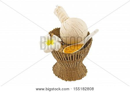 Spa herbal compressing ball white frangipani flowers (Plumeria spp Apocynaceae Pagoda tree Temple tree) turmeric powder in white spoon and candle on bamboo basket isolate on white background.Saved with clipping path