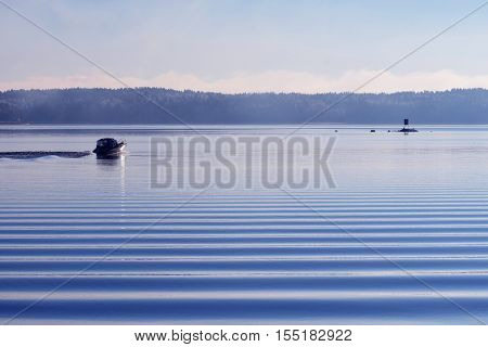 Motorboat on calm cold sea with beautiful small waves in foreground.