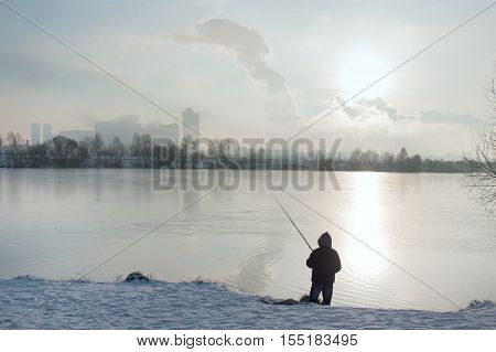 Silhouette of a fisherman against the urban scape outdoor shot with focus in the foreground