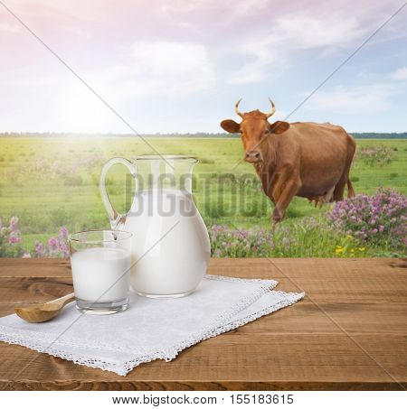 Milk jug and glass on wooden table over cow meadow