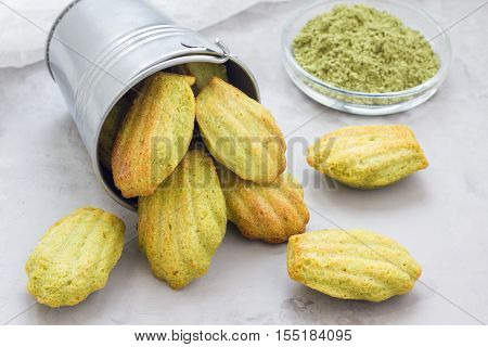 Homemade matcha green tea madeleines on the table and in metal bucket horizontal