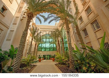 DUBAI, UAE - OCTOBER 14, 2016: The interior of the luxurious Al Qasr Hotel with palm trees.  The Al Qasr Hotel is part of the Jumeirah Group of hotels