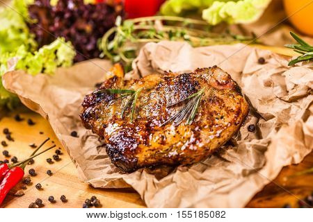 Grilled pork chop with spices and herbs on parchment paper