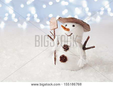 Happy snowman decoration on blue bokeh background