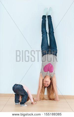 Little girl follows her elder sister doing a handstand